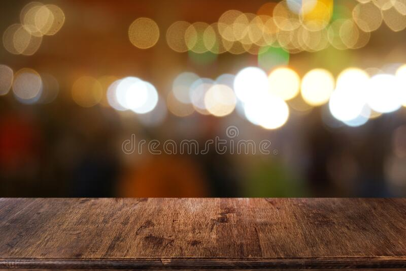 Empty dark wooden table in front of abstract blurred bokeh background of restaurant. stock image