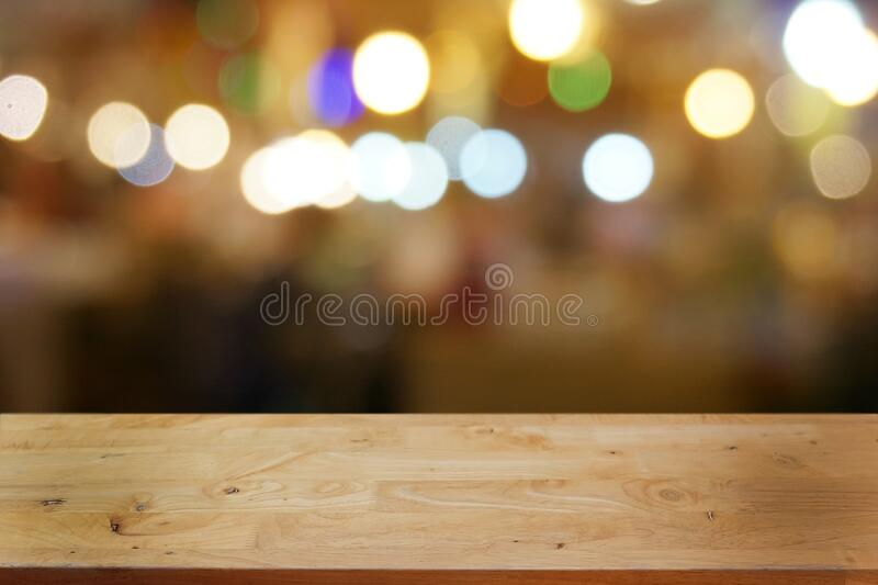Empty dark wooden table in front of abstract blurred bokeh background of restaurant. royalty free stock photography