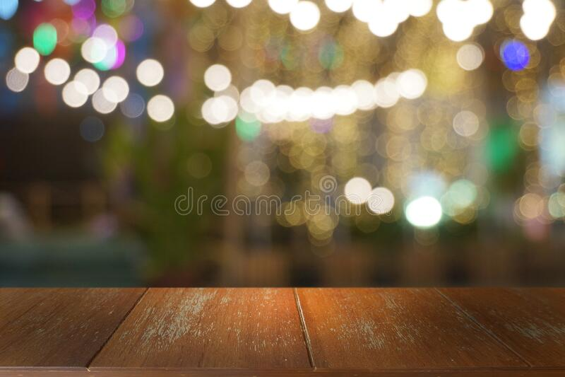 Empty dark wooden table in front of abstract blurred bokeh background of restaurant. royalty free stock image