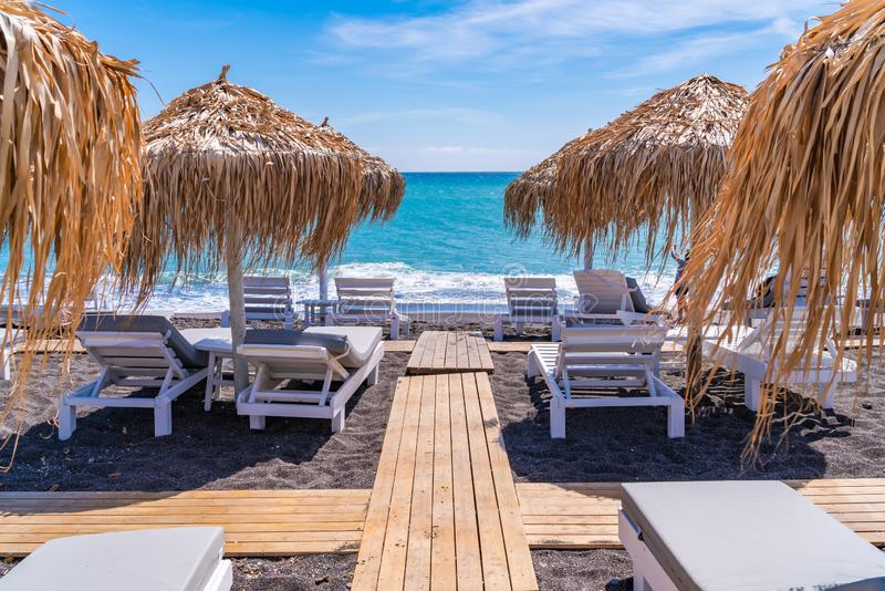 Empty deck chairs and umbrellas on the black sand beach in Perissa stock photos