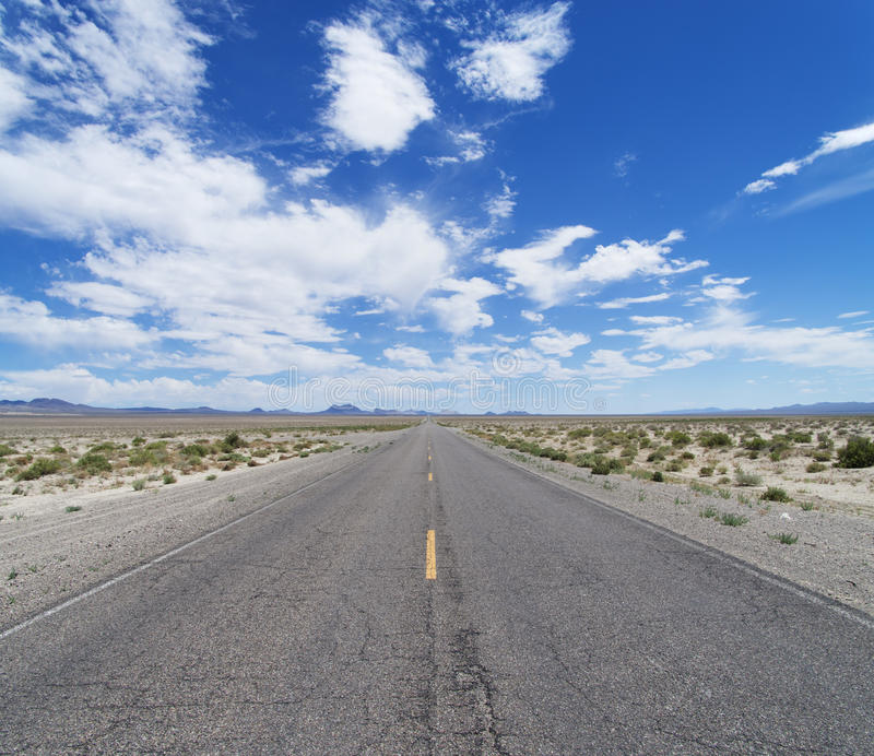 Empty Desert Road. An empty desert road cust across Nevada to the horizon under a partly cloudy blue sky royalty free stock images