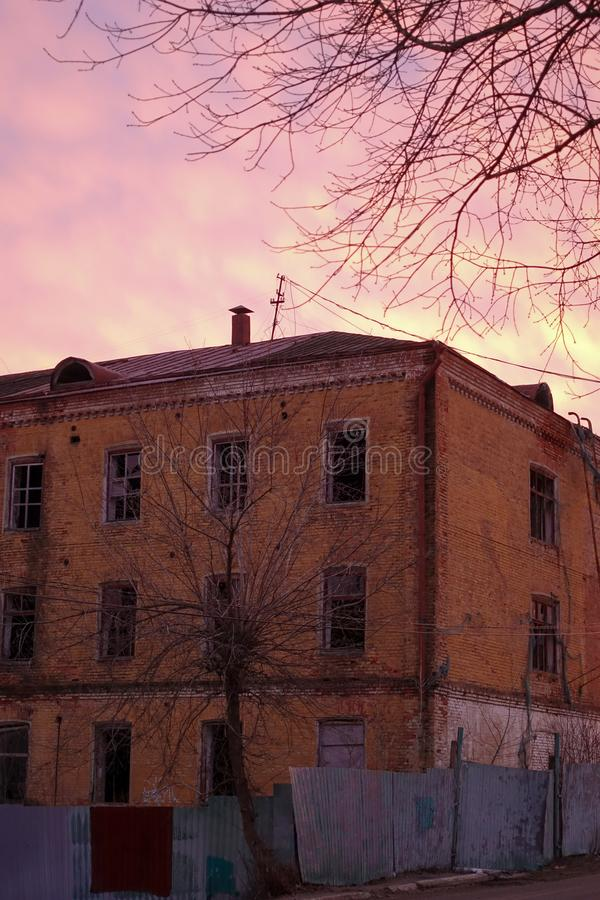 Empty destroyed building with broken windows. Pink sky Sunset. Photo in red colors. The oppressive atmosphere of destruction. Scenery for a horror movie royalty free stock photos
