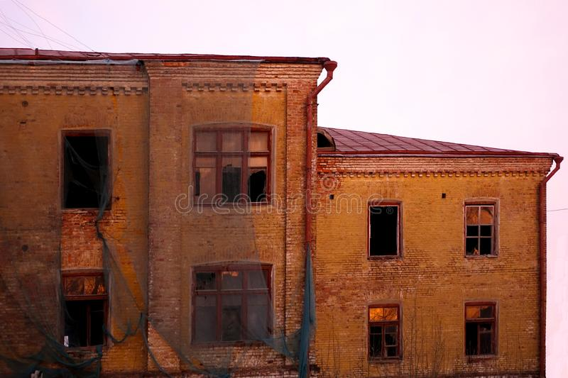 Empty destroyed building with broken windows. Pink sky Sunset. Photo in red colors. The oppressive atmosphere of destruction. stock photos