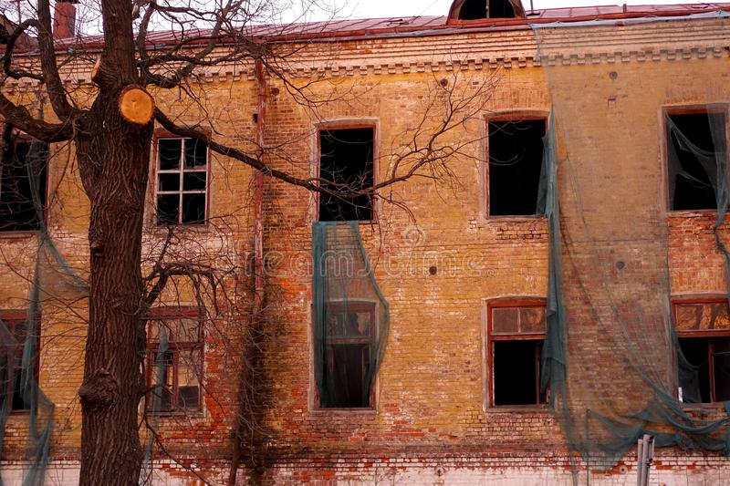 Empty destroyed building with broken windows. Pink sky Sunset. Photo in red colors. The oppressive atmosphere of destruction. stock photography