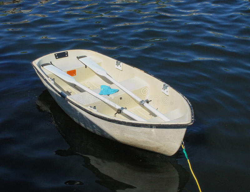 Empty Dinghy. Empty white dinghy alone on the water and rope dangling stock photo