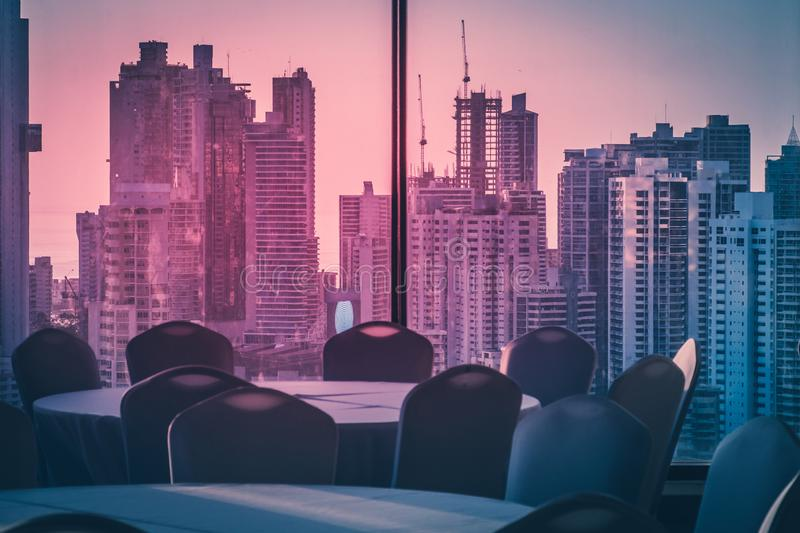 Empty dinner table in room with view over modern skyline during stock image