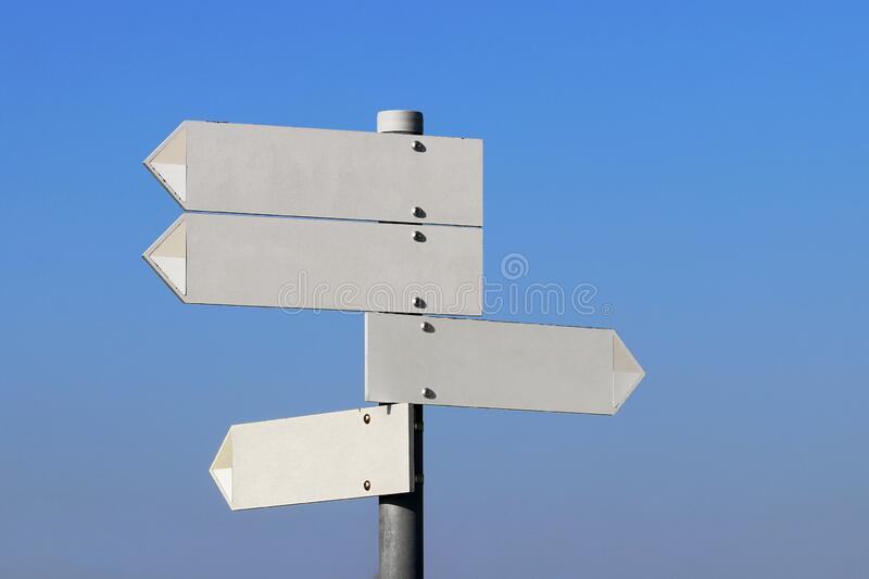 Empty directional signs in front of a blue sky stock images