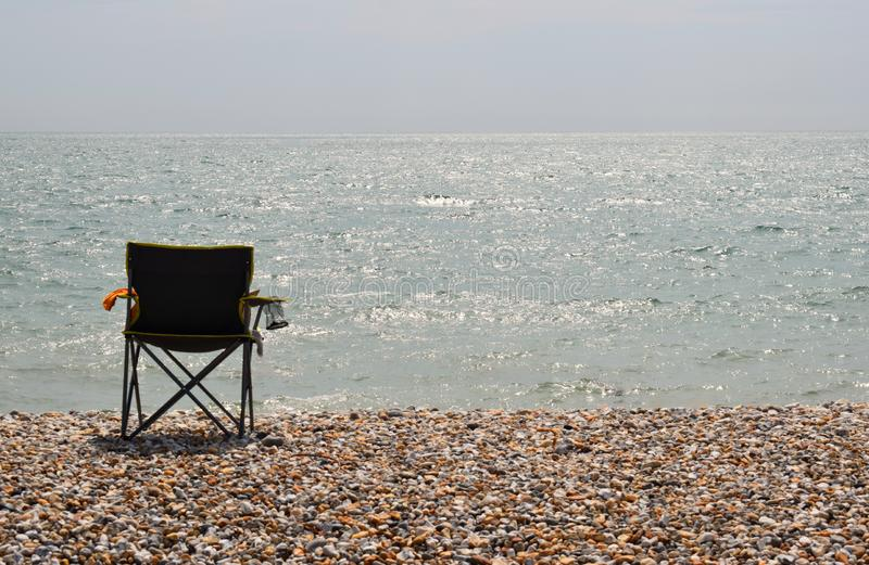 An empty Director`s Style chair on a beach facing the ocean. An empty chair on a deserted pebble beach facing the sea royalty free stock photography