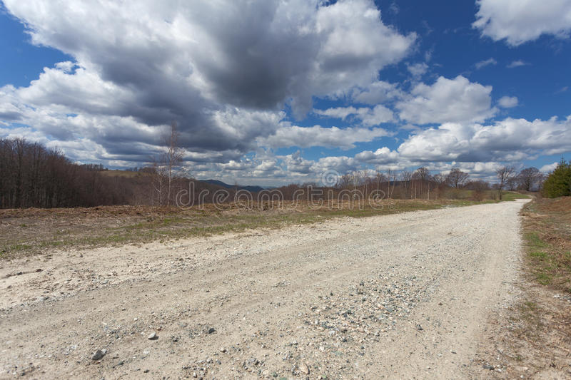 Empty dirt road in mountain at sunny day stock photography