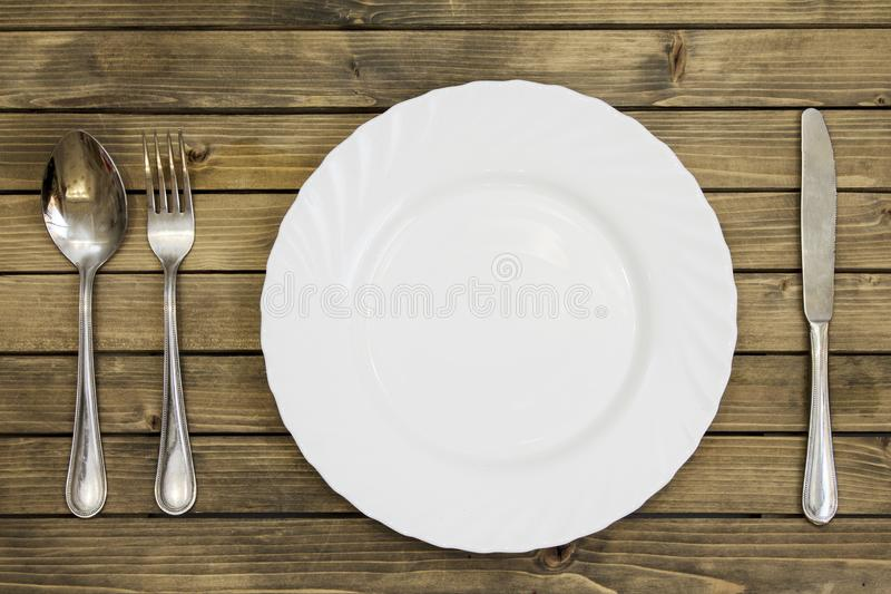 Empty dish and cutlery on wooden background closeup. Empty dish and cutlery on wooden background close up view from top. Dinner set royalty free stock image
