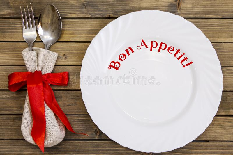 Empty dish and cutlery on wooden background closeup. Empty dish and cutlery on wooden background close up view from top. Dinner set with text or lettering. Bon stock photo