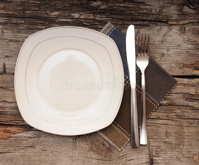 Empty dish, knife and fork and brown napkin. On old wood table stock photos