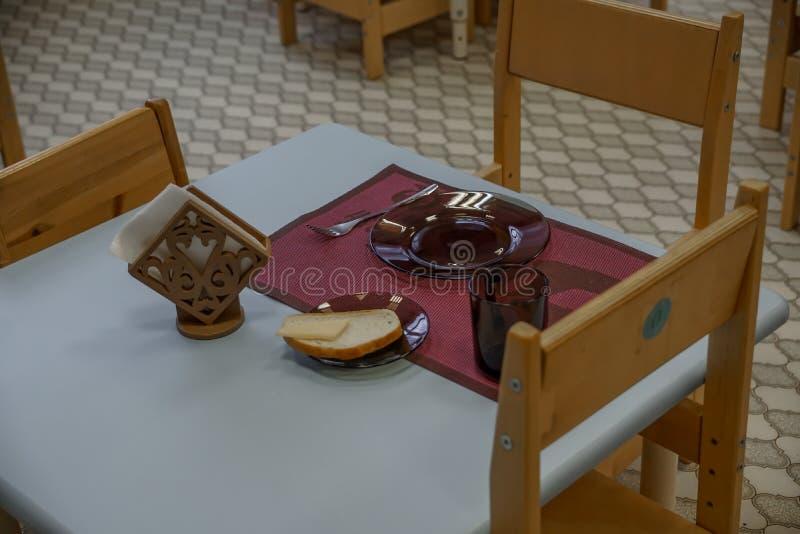 Empty dishes set for breakfast in kindergarden. Kindergarten indoor view. Chairs and tables. Furniture. stock image