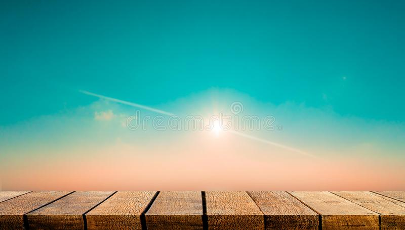 Empty wooden board shelf table counter with copy space for advertising backdrop and background with sun flare on teal sky. Empty display wooden board shelf table stock images