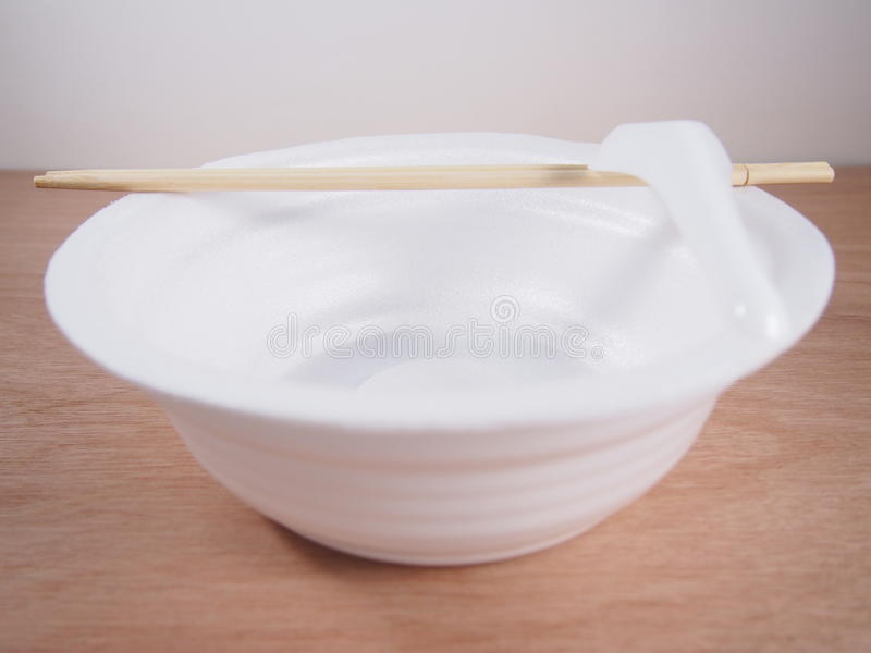 Empty disposable foam bowl with kitchen ware equipment. On wood background royalty free stock images