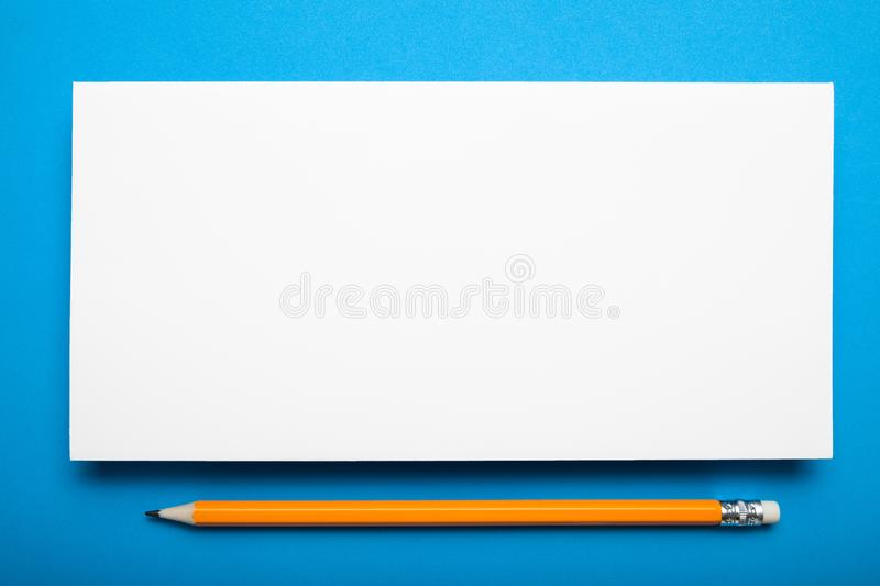 Empty DL flyer on a blue background with a pencil. Mock up.  royalty free stock image