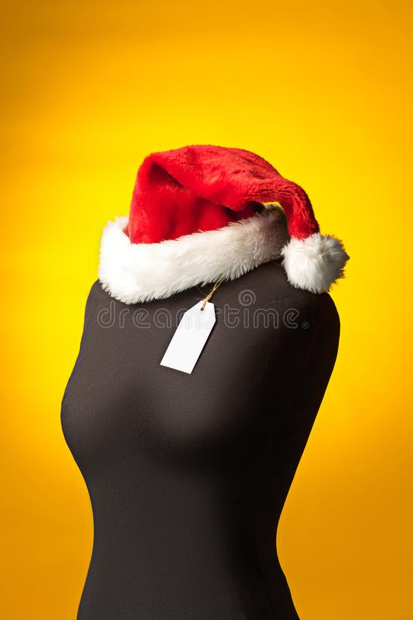 The empty dummy, sale price tag hanging from the button hole. The empty dummy with Santa hat, sale price tag hanging from the button hole. The shopping and sale royalty free stock photography