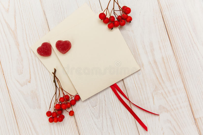 Empty envelopes with red rowan and stripe.Two red hearts jujube.White wooden table.Mokup with empty space stock image