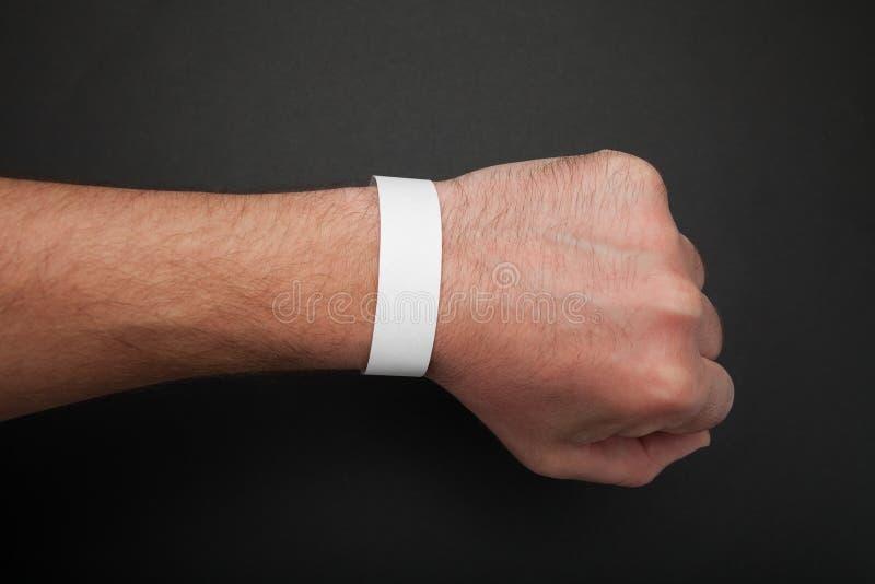 Empty event ticket wrist band design. Concert blank paper wristband, bracelet mockup on black background.  royalty free stock photo