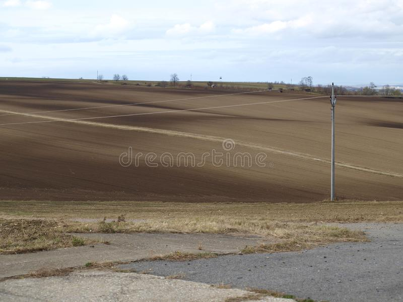 Empty field of brown ground. With electricity lines in front and trees in background stock photos