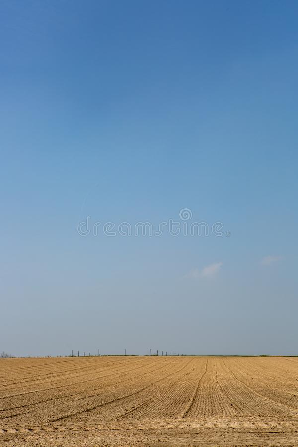 An empty field under a clear blue sky royalty free stock photography