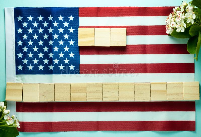 Empty fifteen wooden cubes laid out on American flag near blooming branches stock photography