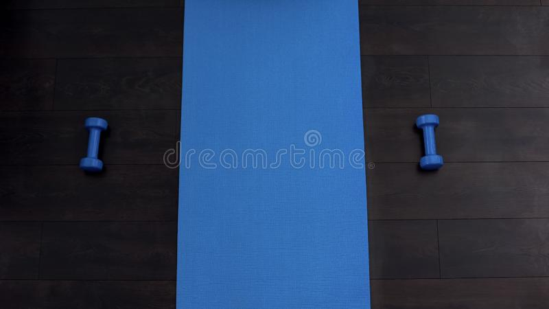 Empty fitness mat on floor of gym, dumbbells lying on both sides, training. Stock photo royalty free stock photo