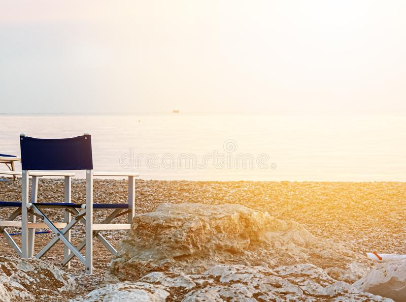 Empty folding outdoor chair on a pebble beach lit by the dawn light over the sea. Calm scene royalty free stock images