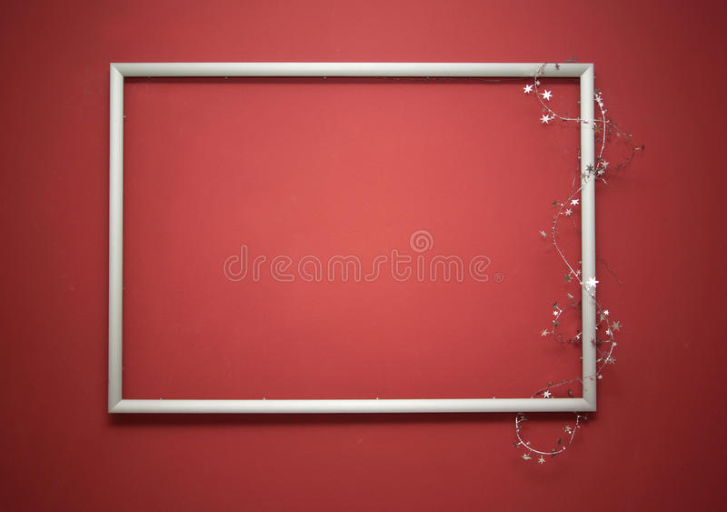 Empty frame. With christmas garland on the red wall stock images