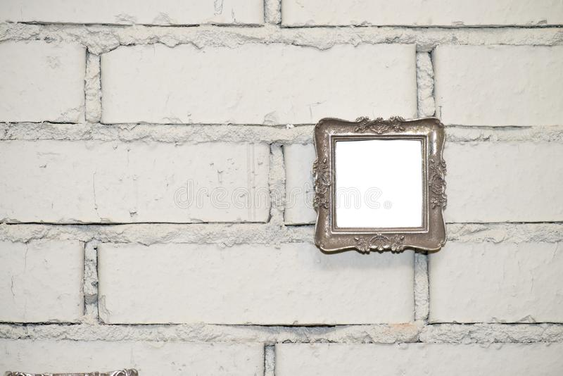 Empty frame on a white brick wall. Empty vintage photo frame on a white brick wall, copy space royalty free stock photography