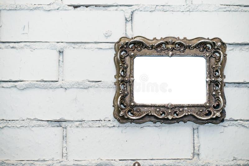 Empty frame on a white brick wall. Empty vintage photo frame on a white brick wall, copy space stock photo