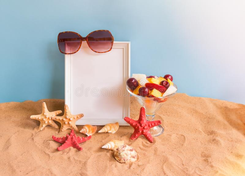 Empty frame for your text, bowl of fruit salad, sunglasses, starfishes and seashells on sand beach on blue backdrop. Summer beach holiday concept royalty free stock image