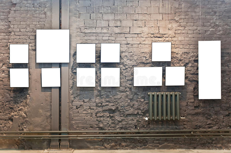 Empty frames on brown brick wall and radiator stock photos