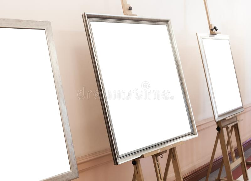 Blank empty frames on painting easel, background. Empty frames on painting easel, blank background royalty free stock photography