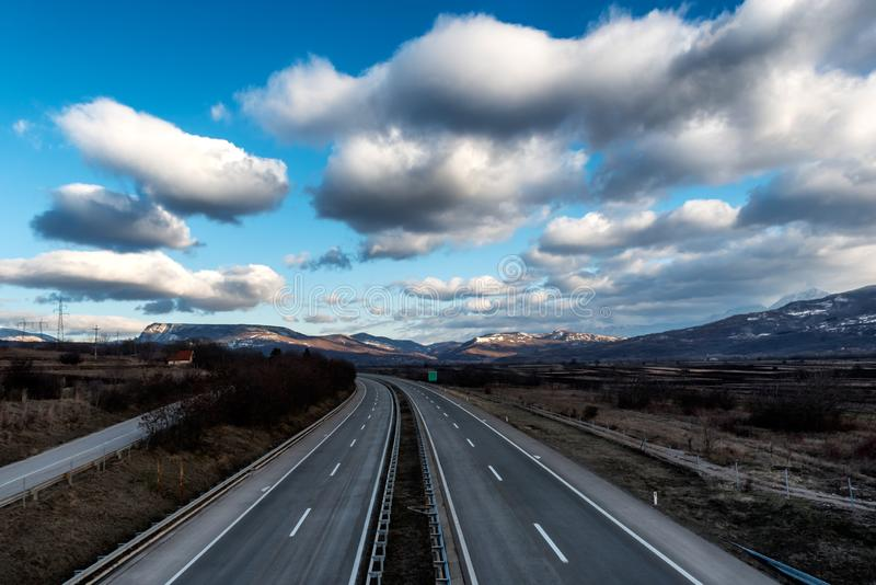 Empty freeway or motorway with beautiful dramatic sky royalty free stock photo