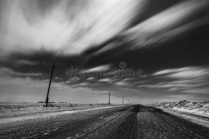 Empty freeway at night. Black and white. Road to the horizon. Clouds, rapidly running across the sky. stock photography