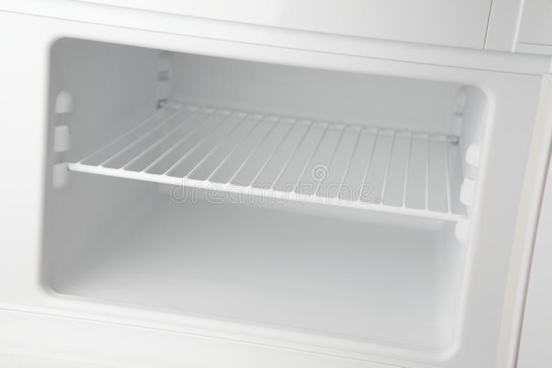 Empty Freezer. A clean and empty freezer section of a modern refrigerator with white walls and a metal shelf royalty free stock photo