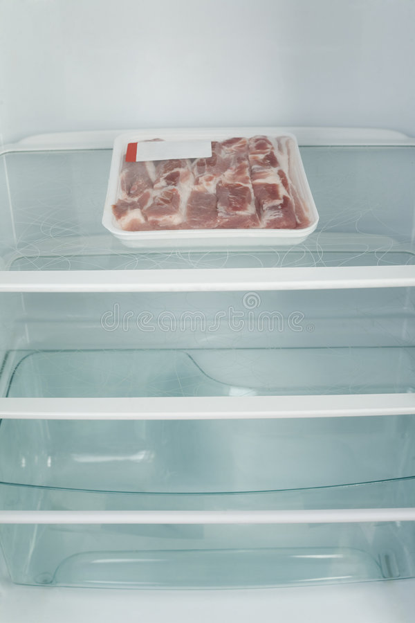 Almost empty fridge. Wrapping meat in fridge. Front view stock photo