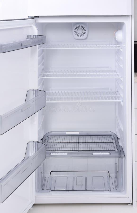 Empty fridge. Opened, empty fridge, standing on white floor royalty free stock image