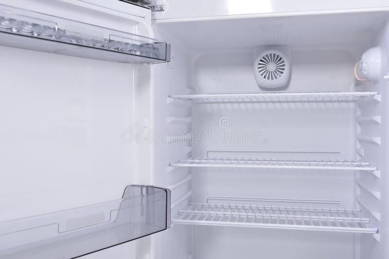 Empty fridge. Opened, empty fridge, standing on white floor royalty free stock photography