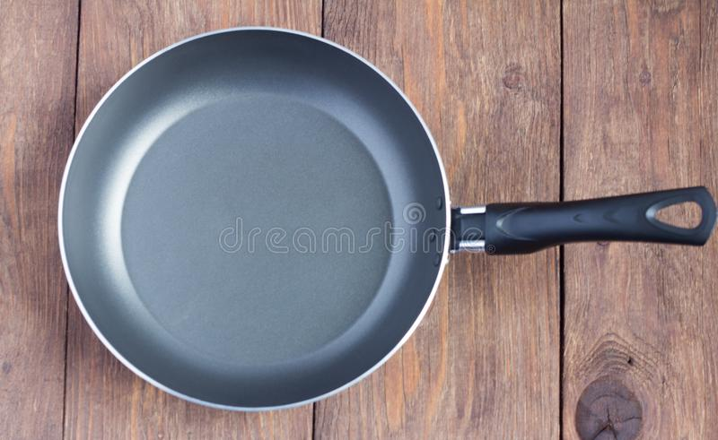 Empty frying pan with non-stick coating on wooden background.  stock photo