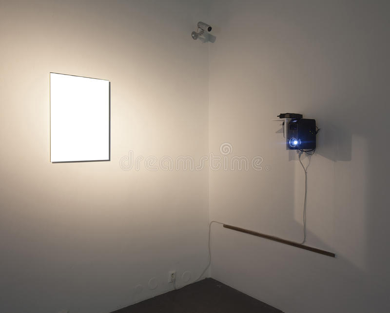 Empty gallery. Real empty frame and projector at gallery plaster wall stock photography