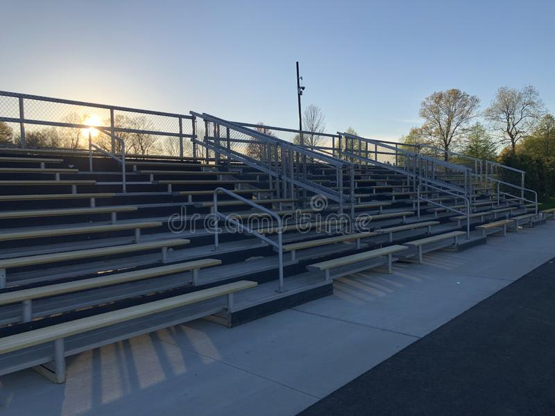 Quiet bleachers after the game is over. Empty game field. Football game is over. Bleachers are quiet. Empty bleachers. each. People have gone home. Sun is royalty free stock photo