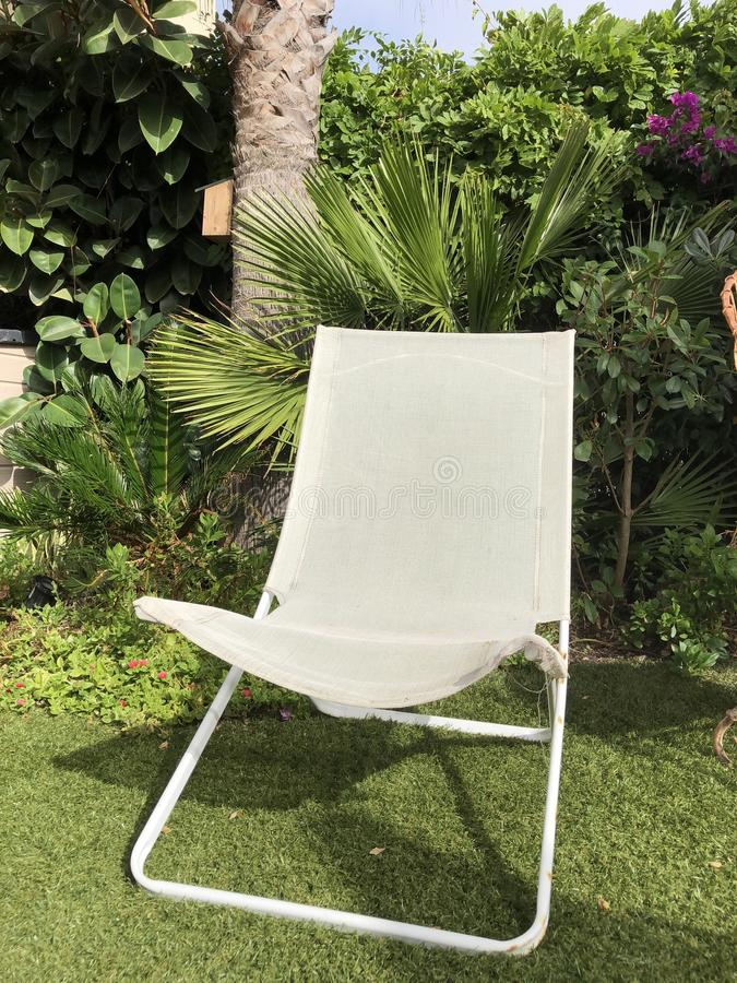 Empty garden chair. An empty white garden deck chair on the lawn with a backdrop of plants and bushes royalty free stock photos