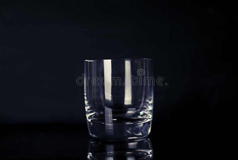 Empty glass on black stock photography