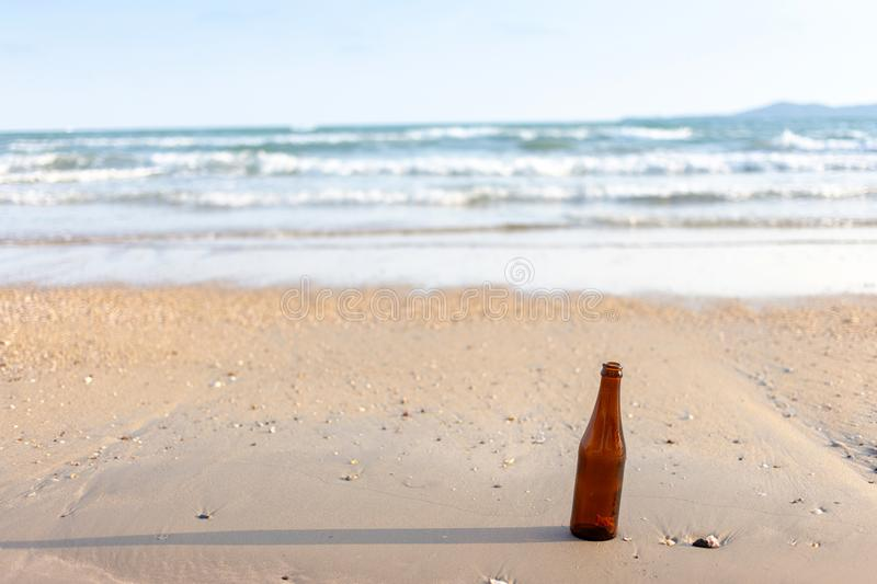 empty glass bottle on beach .Dirty refuse enviroment with people royalty free stock image