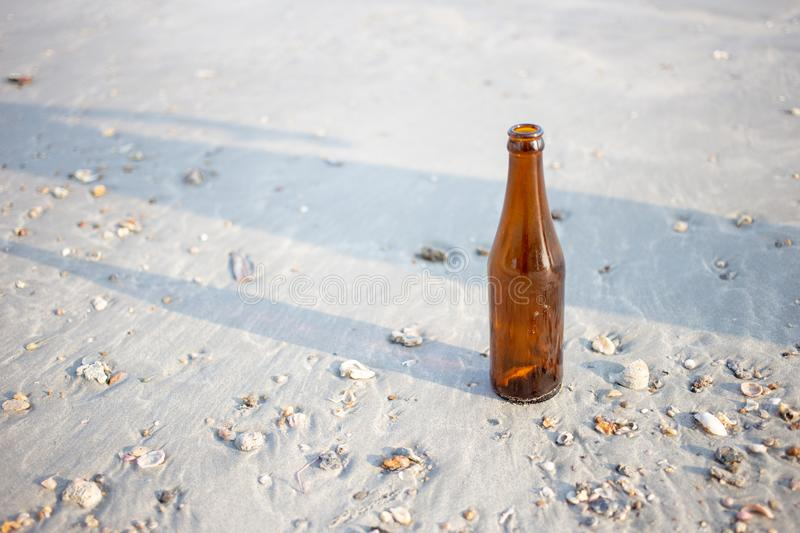 empty glass bottle on beach .Dirty refuse enviroment with people royalty free stock photo