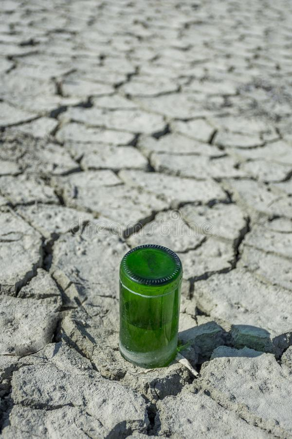 An empty glass bottle is found at the bottom of a dry salt lake. Human litters everywhere. 