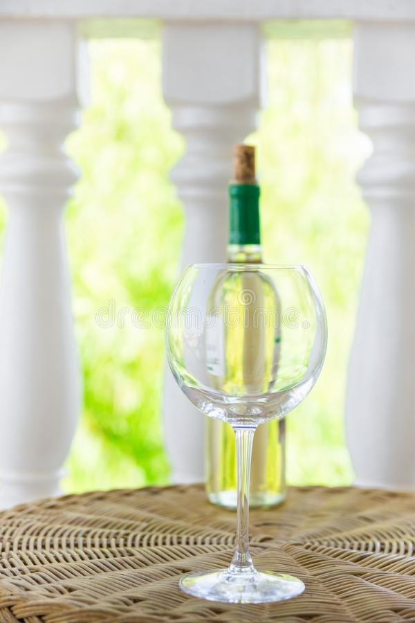 Empty glass bottle with white dry wine on wicker table on garden terrace of villa or mansion. Authentic lifestyle image stock photo