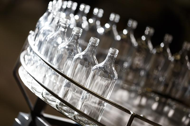 Empty glass bottles on the conveyor. Factory for bottling alcoholic beverages. Many bottles on conveyor belt in glass factory. Factory for bottling alcoholic royalty free stock photography